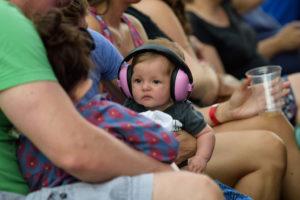 Un bébé avec un casque anti bruit dans une fête en plein air