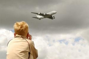 enfant se bouchant les oreilles à cause du bruit d'un avion